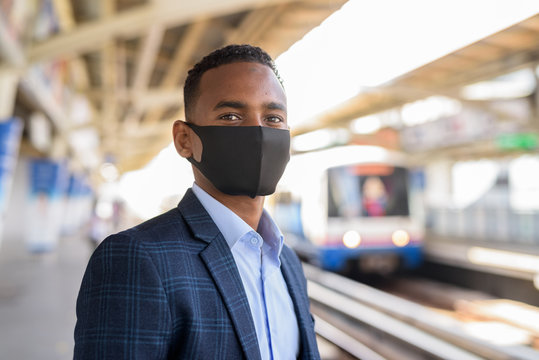 Young African businessman with mask for protection from corona virus outbreak thinking and waiting at sky train station