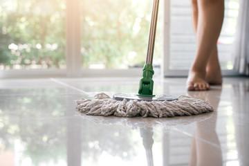 Asian women cleaning folk using mop tiles.