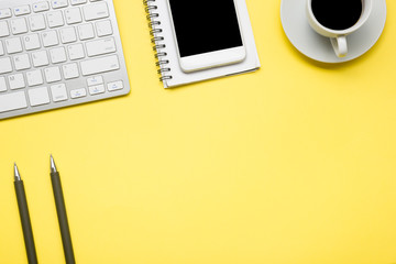 Yellow desk office with laptop, smartphone and other work supplies with cup of coffee. Top view with copy space for input the text. Designer workspace on desk table essential elements on flat lay