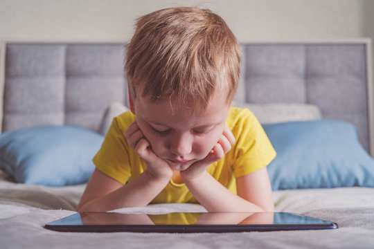 Distance education, learning. Boy is lying on the bed with a tablet in the room. Child with a gadget. Teenage child using tablet pc.