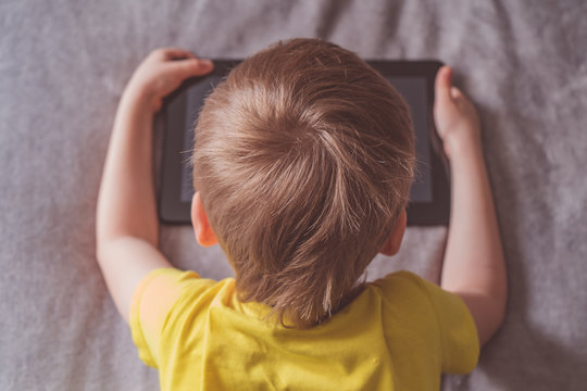 Distance education, learning. Boy is sitting on the bed with a tablet in the room. Child with a gadget. Teenage child using tablet pc.