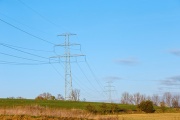 Steel high voltage poles and electric wire with blue sky and fields in rural areas.