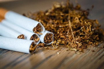 cut tobacco leaves and handmade cigarettes on a wooden background