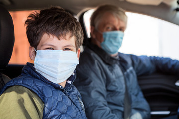 Preteen age boy sitting on passenger seat with his father as driver, men wearing surgical masks against coronavirus, looking at camera