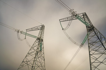 Power transmission pylons against a cloudy sky