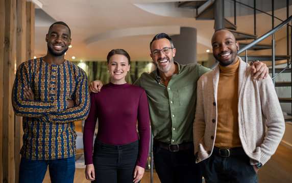 Smiling group of businesspeople standing together in a modern of