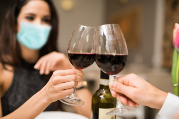 Masked couple toasting wineglasses in a restaurant during coronavirus pandemic