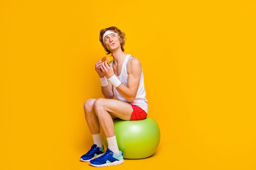 Portrait of his he nice attractive funky sportive guy sitting on fitball eating tasty yummy food...