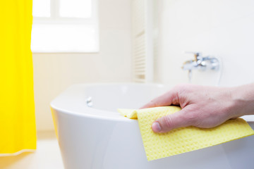 Hand cleaning a tub with a yellow wipe in a bright bathroom