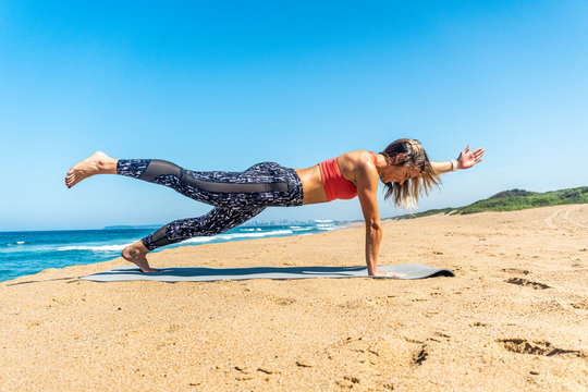 young woman  doing pilates exercises on the beach: Superman hold.
