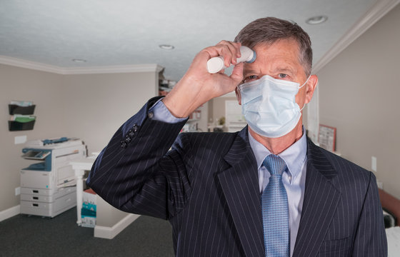 Mockup of senior adult wearing mask checking for a coronavirus fever with thermometer before going into office for meeting