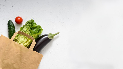 Vegetables, red and green peppers, eggplant, cucumber, lettuce and a rubber glove lie on a paper bag on isolated background. Top view copy space. Donation. contactless food delivery.