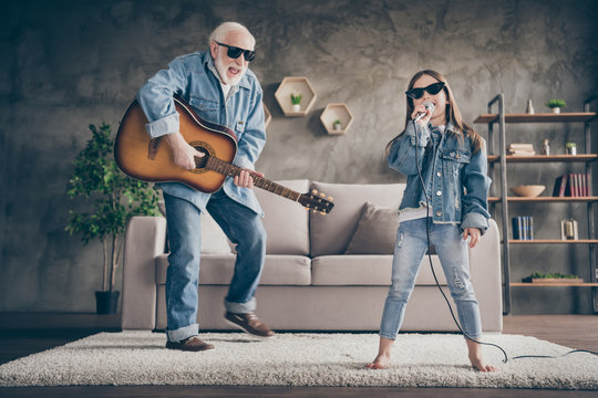Photo of two people grandpa play guitar small granddaughter mic singing rejoicing cool style trendy sun specs denim clothes repetition school concert stay home quarantine living room indoors