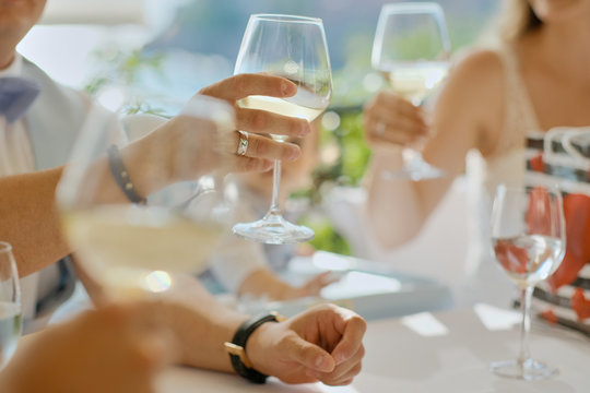 People hands with glasses of wine or champagne at a table on the terrace. Friends meeting