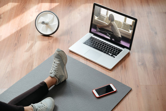 Closeup of young fit woman training indoors using laptop for watching yoga classes online. Home online workout. Home fitness during pandemic, quarantine and self isolation