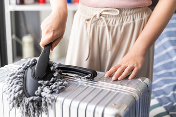 Close up young Asian woman holding dust cleaner mop cleaning suitcase while quarantine