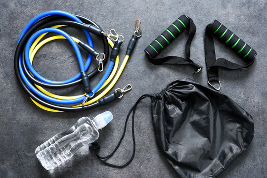Sports accessories - an expander with a carbine and water on a black background. Fitness.