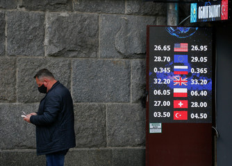 A man wearing a protective face mask counts money near a currency exchange office in Kiev