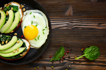 Sandwich with avocado, spinach and fried egg in a pan. Dark  wooden background and place for an inscription.