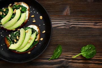 Sandwich with avocado, spinach  in a pan. Dark  wooden background and place for an inscription.