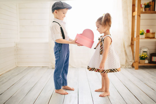 Cute boy gives a beautiful girl a gift. Little boy and girl in the room. Love concept.
