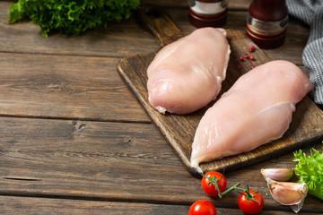 Foto op Canvas Kip Chicken breast fillet on a wooden Board on a brown wooden table. Raw chicken breast