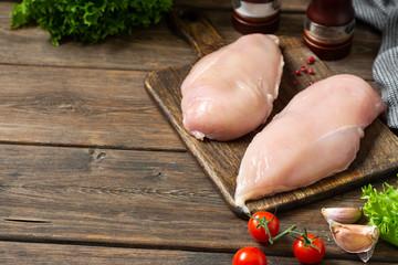 Foto op Aluminium Kip Chicken breast fillet on a wooden Board on a brown wooden table. Raw chicken breast