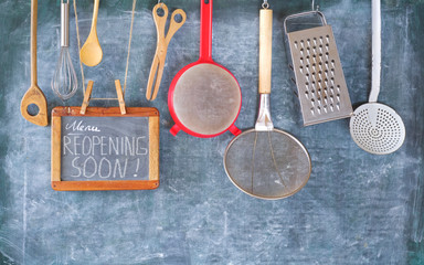 Restaurant display,announcing reopening after the corona lockdown,cooking, culinary concept message reopening soon on blackboard.