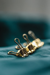 Closeup macro photo of golden office pin. Conceptual picture with group and one apart from all