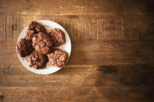 Dark chocolate cookies on a raw wooden table