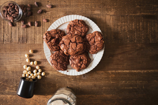 Homemade dark chocolate cookies with macadamia nuts cocoa beans and sugar on a rustic wooden table
