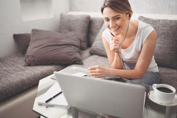 Attractive happy young student studying online at home, using laptop computer, headphones, having video chat, waving. Remote work, distance education. Video conference or virtual event on quarantine