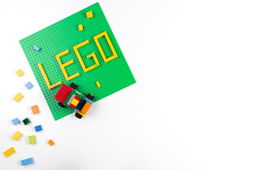 Vilnius, Lithuania - 17 August, 2019: Word LEGO on green baseplate and colorful Lego blocks on white background