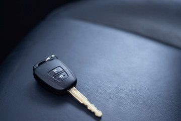 Close up of a car key ring and remote control alarm system charm in  new vehicle interior. or...