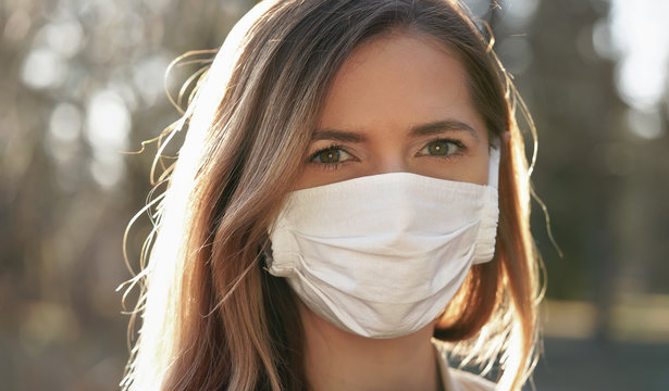 Young woman wearing white cotton virus mouth nose mask in park, sun lit blurred yellow leaves trees, in background, closeup face portrait