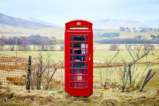 Bright red iconic British telephone box. This old fashioned phone booth is in a rural landscape beside country lane, with fields and Scottish hills in the background.