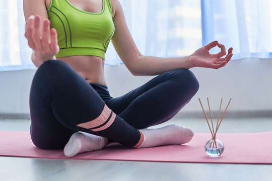 Fitness woman wearing sportswear in lotus position with aroma sticks and essential oil bottle on mat during yoga training, aromatherapy and meditation. Mental health