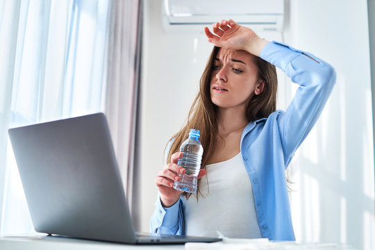 Sweating working woman suffering from heat, hot weather and thirst cools down with refreshing cold water bottle during online remote work at computer at home. Refresh concept