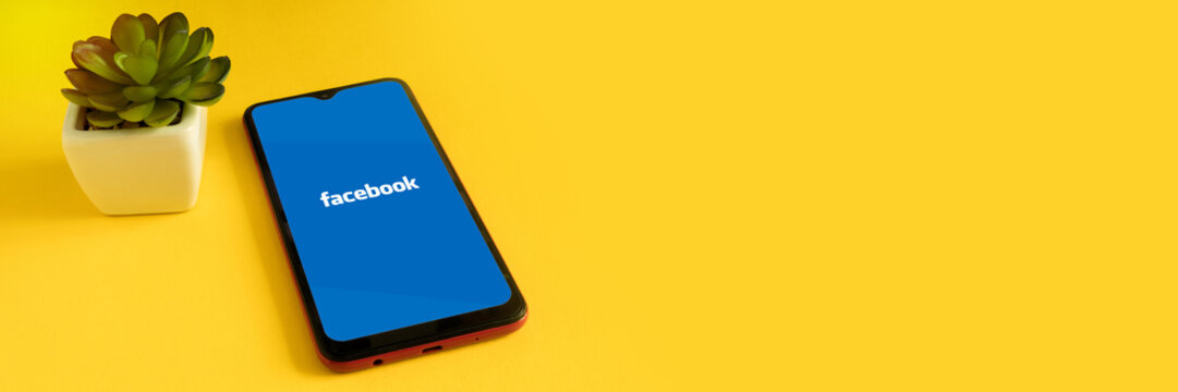 Minsk 12.05.2020. Smartphone on a yellow background with image of Facebook.