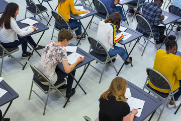 High school students taking exam at desks in classroom