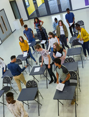 View from above high school students finishing exam at desks
