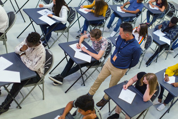 Teacher supervising high school students taking exam at desks