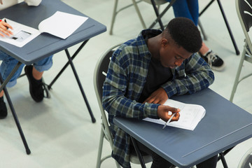 Focused high school boy student taking exam at desk in classroom