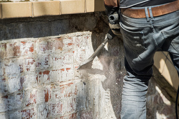 Man removes tiles from a wall