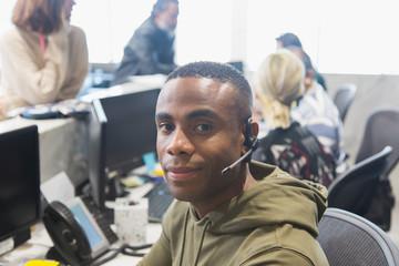 Portrait confident male call center representative in office