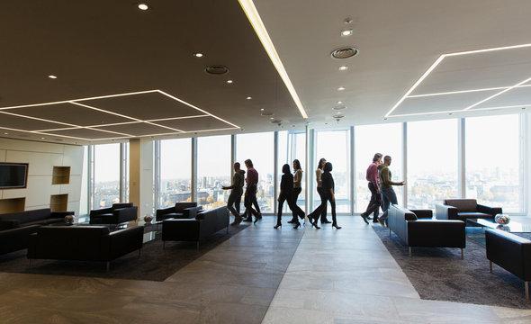 Business people walking in modern office lobby