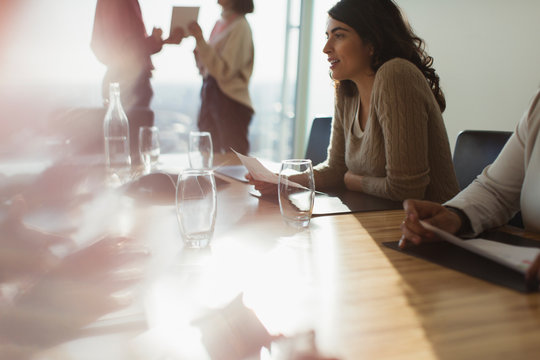 Business people talking in sunny conference room meeting