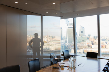Silhouette businessman standing at urban highrise office window