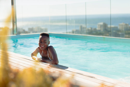 Happy young woman in sunny, luxury swimming pool