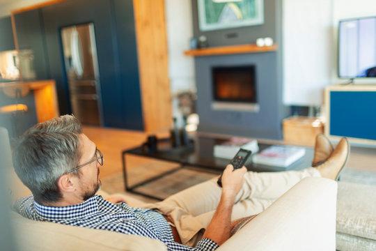 Man relaxing, watching TV in living room